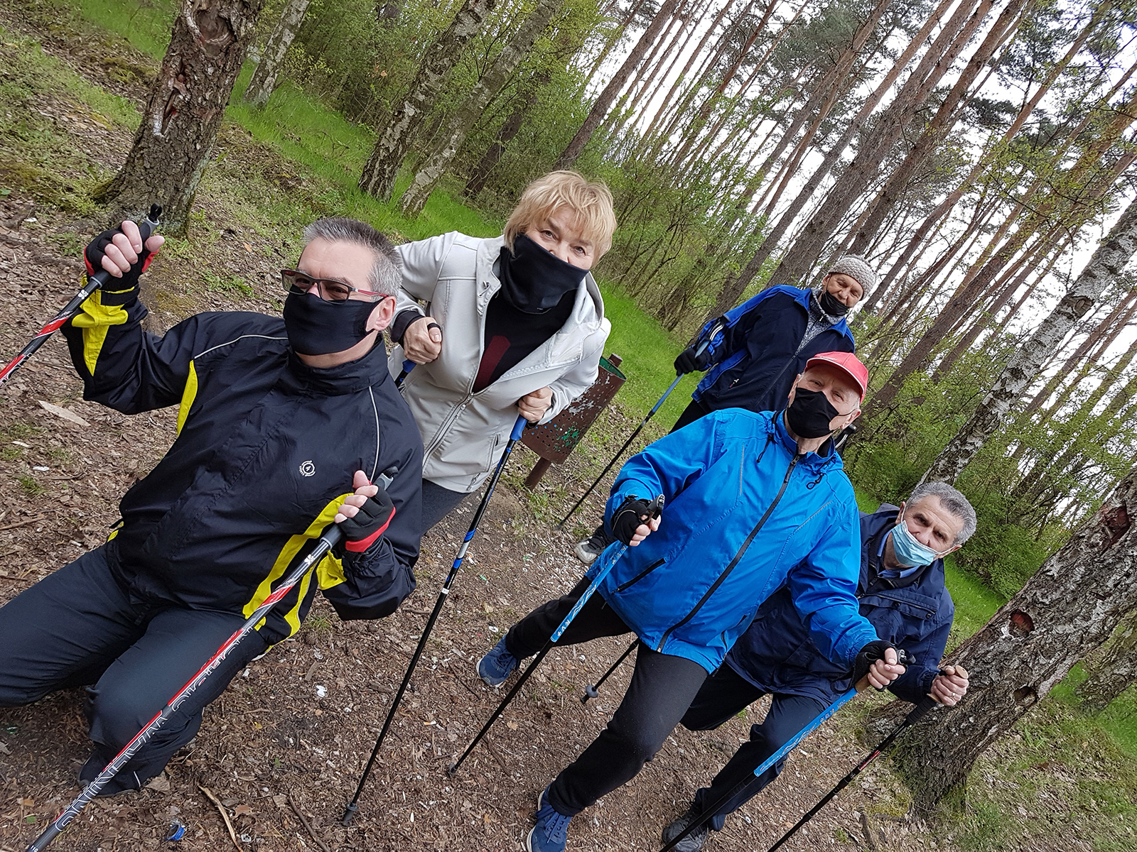 grupa osób w sportowych strojach w lesie pozująca do zdjęcia z kijkami