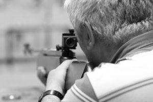 mężczyzna trzymający broń i celujący do tarczy